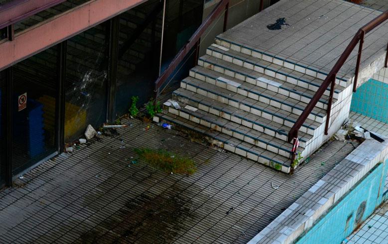 Schodiště zarůstá plevelem, poblíž leží odpadky a spadaná omítka. – Foto: Filip Harzer, Zdroj: Český rozhlas